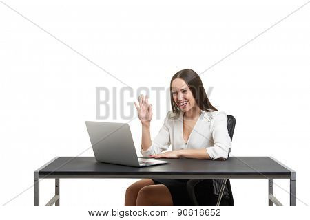 smiley businesswoman have video chat, waving her hand and looking at laptop over white background