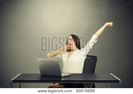 tired woman sitting with laptop and yawning over dark background
