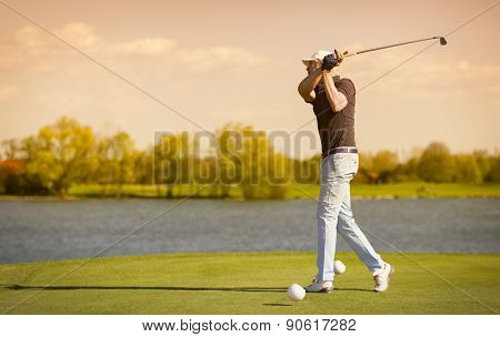 Male senior golf player swinging golf club, with lake in background before sunset.
