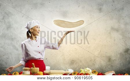 An Attractive Asian Chef Is Cooking Pizza