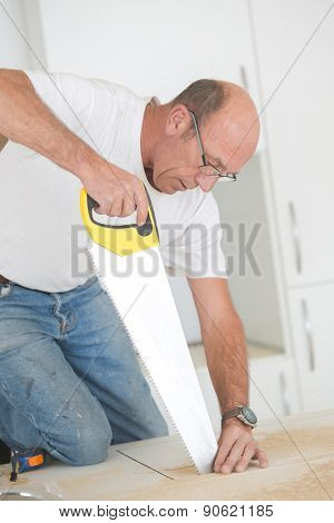 Carpenter using a hand saw