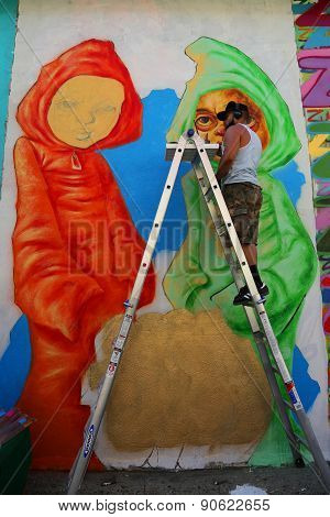 Street artist Bob Plater painting mural at JMZ Walls in Brooklyn