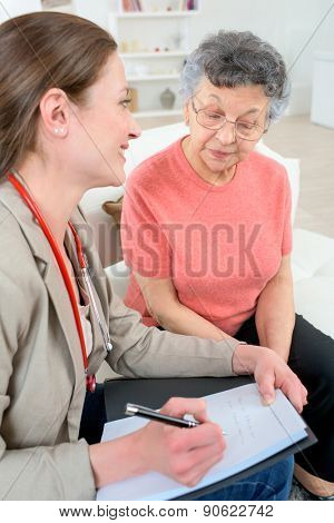 Doctor taking notes as she chats to senior patient