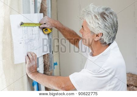 Builder measuring blueprints with tape measure