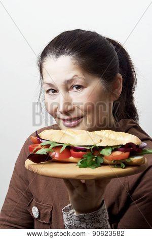 A woman shows a vegetarian sandwich