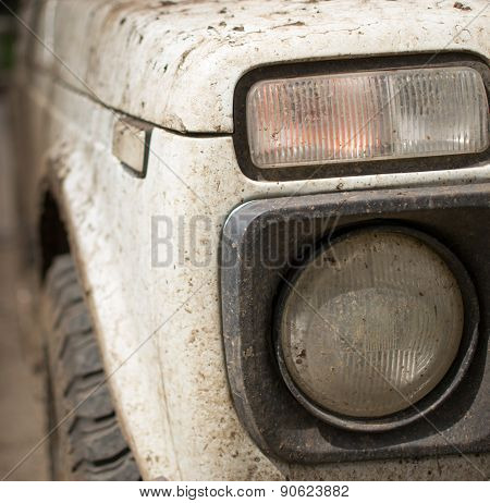 Muddy White Vehicle And Headlight