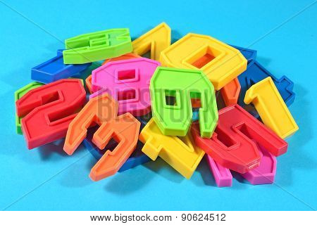 Heap Of Plastic Colored Numbers On A Blue Background