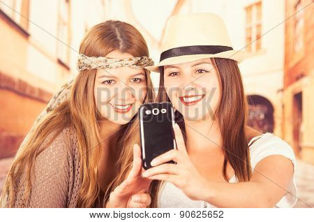 Cute young fashionable girls using cell phone