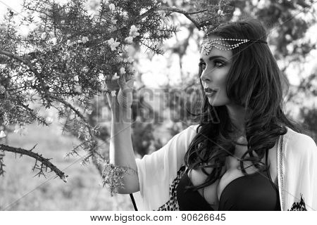 Black and White Head and Shoulders Portrait of Mystical Looking Brunette Woman Wearing Head Band Standing Underneath Flowering Tree