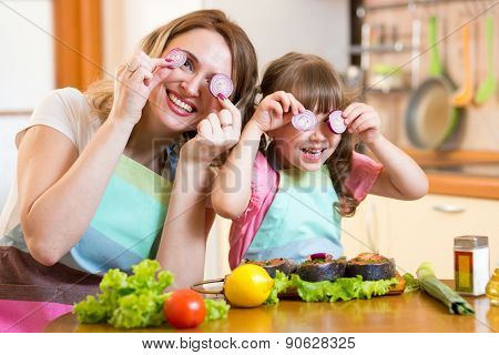 mother and daughter playing with vegetables in kitchen, healthy food