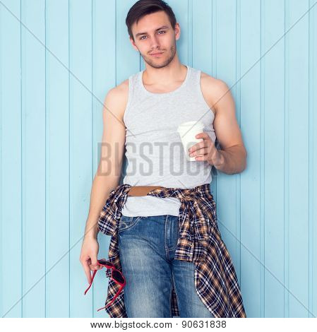 Portrait young man drinking holding paper cup of coffee city casual urban style looking at camera st