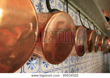 Alignment of saucepans in a kitchen wall