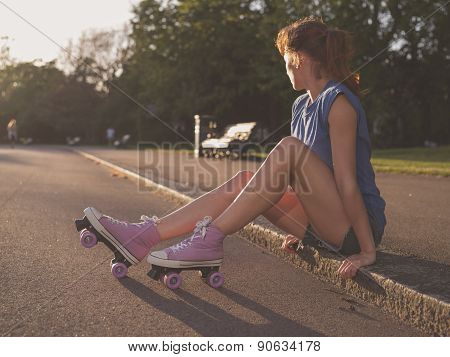 Young Woman Sitting In Park With Roller Skates