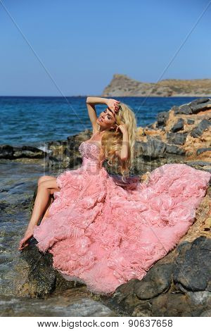 Beautiful Blond Woman Sexy Pink Ballroom Dress Standing On The Rocks In Santorini