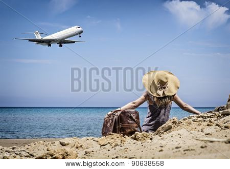 Woman with vintage leather travel bag on the beach looking at an airplane passing by