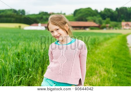 Cute little girl of 7 years old playing in a countryside