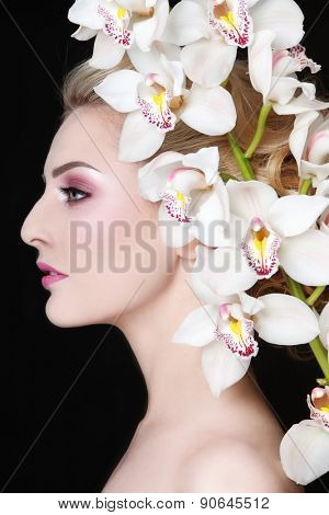 Profile portrait of young beautiful woman with white orchid