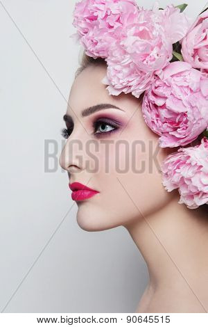 Young beautiful woman with stylish make-up and peonies in her hair