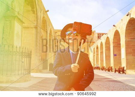 smart little boy taking selfie stick picture while travel in Europe