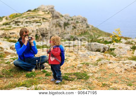 father makinig photo of little daughter while hiking in mountains