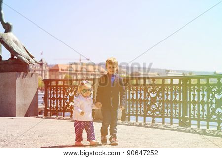 brother and sister walking on quay in summer