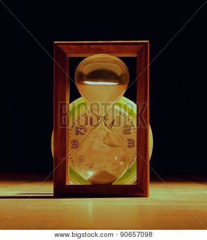 Hourglass against clocks