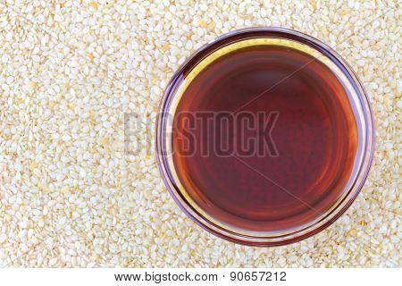 A bowl of cold pressed Sesame oil on white sesame seeds background