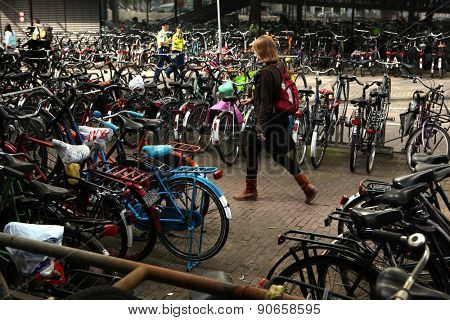AMSTERDAM, NETHERLANDS - AUGUST 9, 2012: Woman walks through the bicycle parking station next to the Central railway station in Amsterdam, Netherlands.