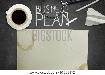Business plan concept on black blackboard with coffee cup
