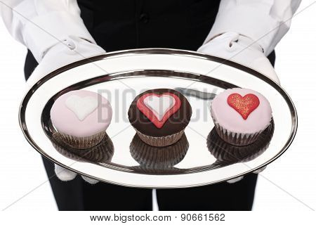butler holding cupcakes