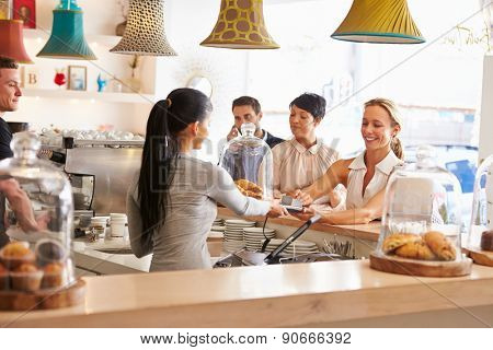 Woman paying for her order in a cafe