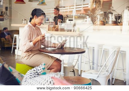Businesswoman using tablet in a coffee shop