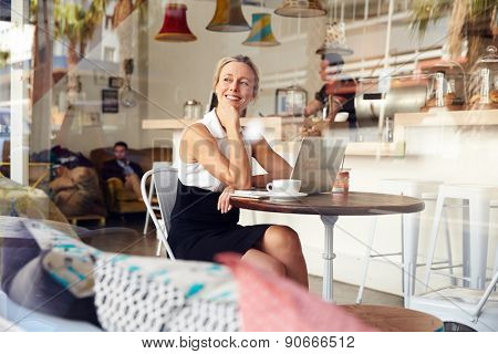 Business woman sitting in small coffee shop