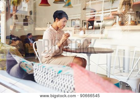 Businesswoman in a coffee shop using tablet