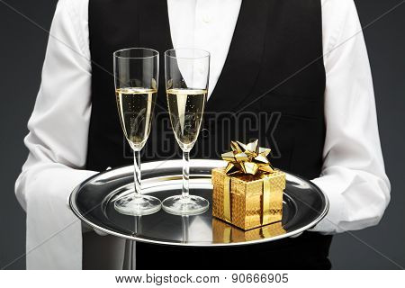 Waiter with two champagne flutes and gift