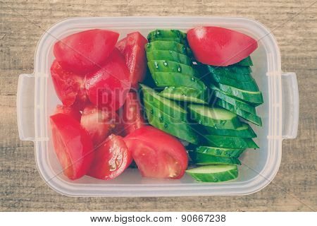 Slice cucumber and slice tomato in plastic lunch box