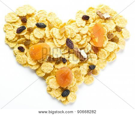 Cornflakes arranged in the shape of heart. Isolated on a white.
