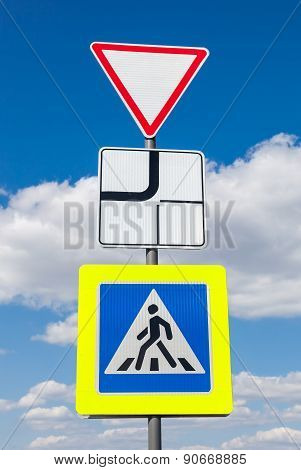 Traffic Signs Main Road And Pedestrian Crossing With Clouds In Background