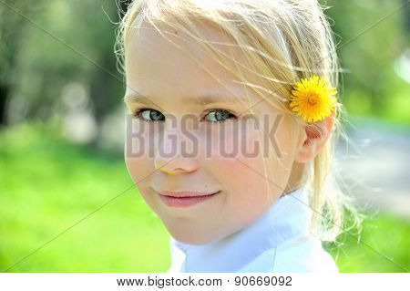 Small girl with dandelion behind her ear