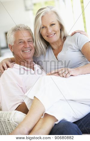 Senior Couple Relaxing In Chair At Home