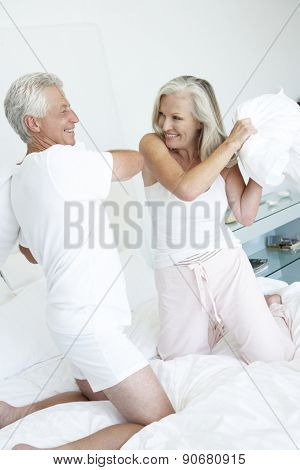 Senior Couple in bedroom having pillow fight