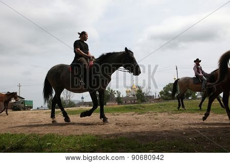 MOZHAYSK, RUSSIA - JUNE 18, 2011: Horse riders in front of the Luzhetsky monastery in Mozhaysk near Moscow, Russia.