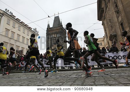 PRAGUE, CZECH REPUBLIC - APRIL 6, 2013: Athletes run past the Old Town Bridge Tower of the Charles Bridge during the Prague international marathon in Prague, Czech Republic.