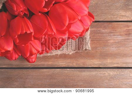Bouquet of red tulips wrapped in sackcloth on wooden background