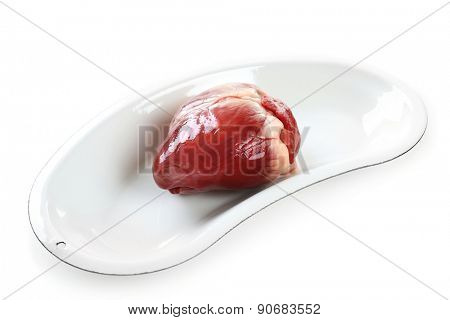 Heart organ in medical metal tray isolated on white