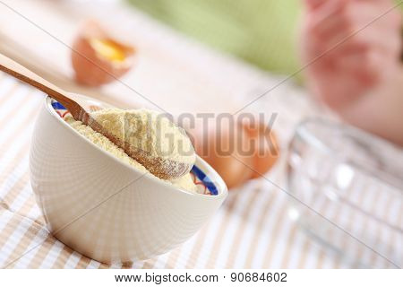 Cornmeal in bowl with wooden spoon on table close up