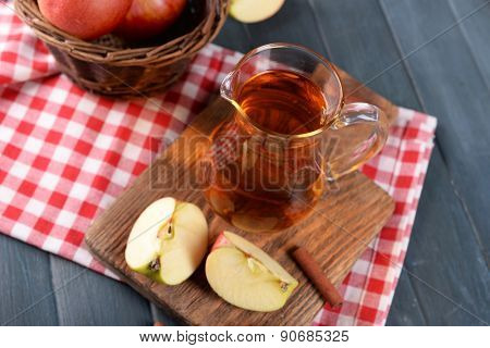 Glass jug of apple juice on wooden table, closeup