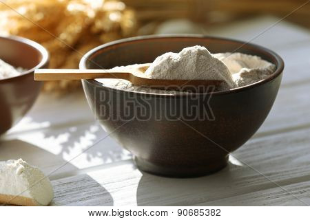 Flour in bowls on wooden planks background