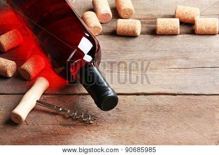 Glass bottle of wine with corks and corkscrew on wooden table background
