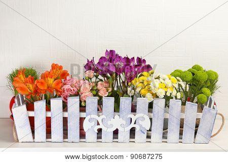 Beautiful flowers in ornamental flowerpot on light background